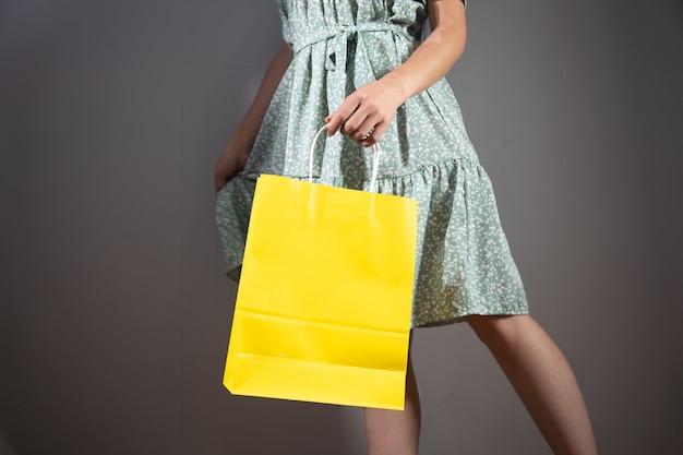 Vrouw in jurk met cadeauzakjes op grijze achtergrond