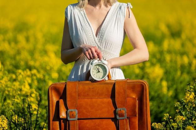 Vrouw in jurk met koffer en wekker in koolzaad veld