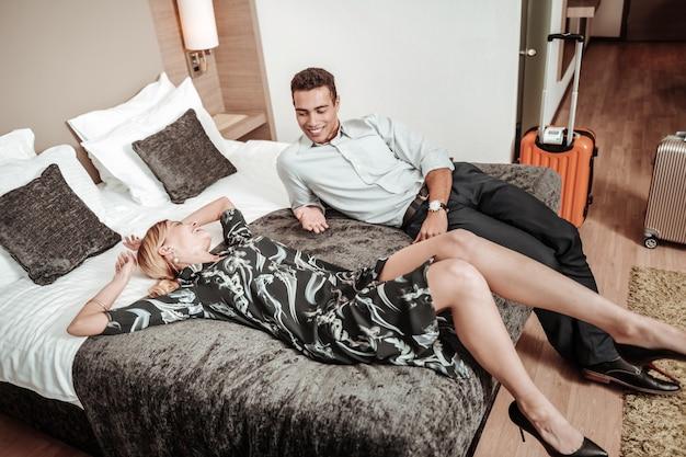Vrouw in jurk. slanke mooie blonde vrouw draagt stijlvolle jurk liggend op bed in de buurt van echtgenoot