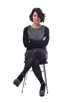 Vrouw in jurk zittend op een witte achtergrond met gekruiste benen en gekruiste armen