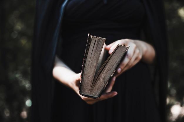 Vrouw in kaap die oud boek opent
