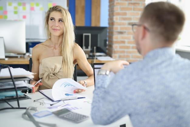 Vrouw in kantoor glimlacht schuldig en houdt commerciële grafiek in haar handen