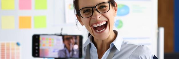Vrouw in kantoor schreeuwt vreugdevol tijdens het filmen van een online uitzending. emotionele uitbarstingen van stemming concept