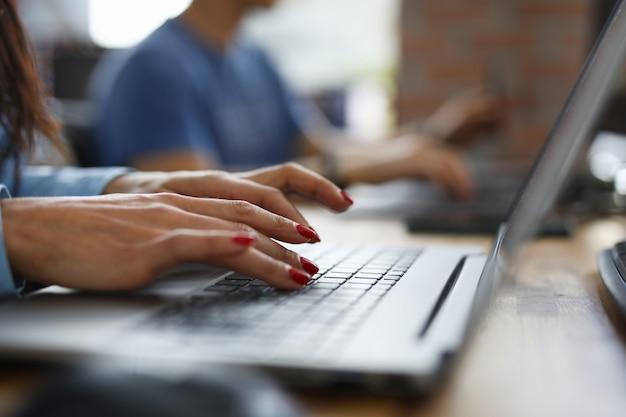Vrouw in kantoor typt op toetsenbord
