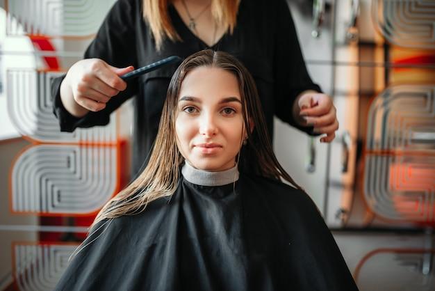 Vrouw in kapsalon, vrouwelijke stylist met schaar en kam in handen. kapsel maken in schoonheidssalon
