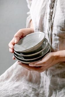 Vrouw in katoenen jurk in handen houden set van lege ambachtelijke keramische kommen dekken door grijze textuur glazuur