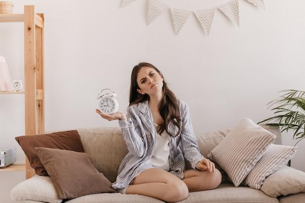 Vrouw in katoenen pyjama zit op een zachte bank en houdt wekker