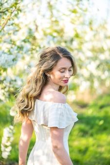 Vrouw in kersen bloeiende boomgaard in de lente