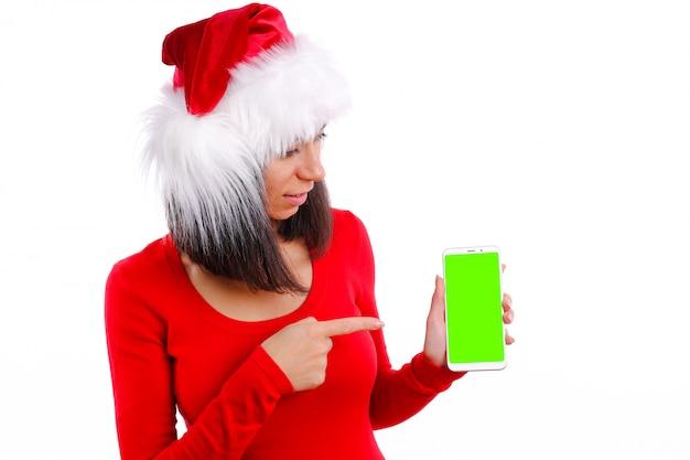 Vrouw in kerst rode jurk en kerstmuts houden smartphone wijzend display