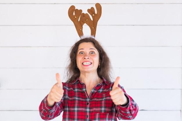 Vrouw in kerstkostuum met herten hoorns op haar hoofd gebaren duimen omhoog
