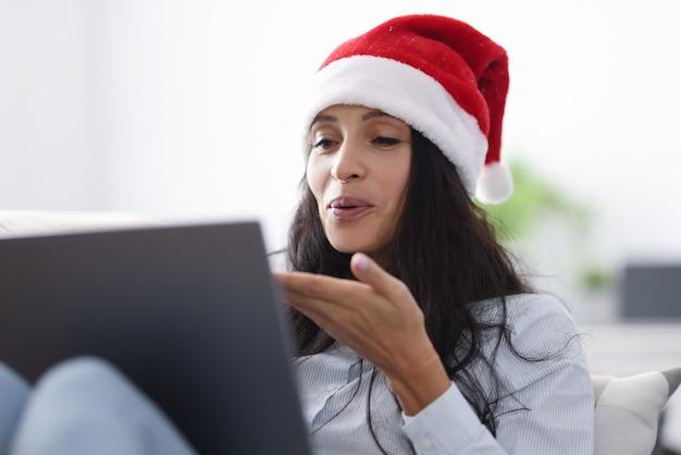 Vrouw in kerstman hoed glimlacht en blaast kus op laptopcomputer