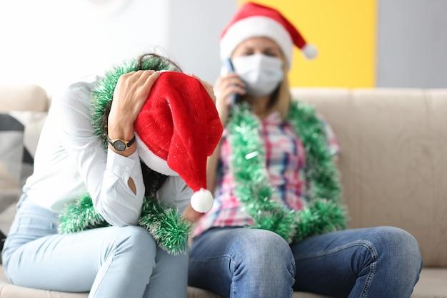 Vrouw in kerstman hoed houdt haar hoofd met handen terwijl vriend in beschermend masker aan de telefoon spreekt