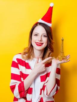 Vrouw in kerstman hoed met eiffeltoren geschenk