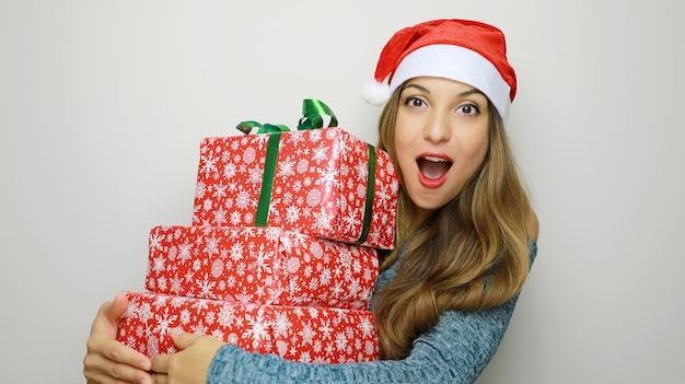 Vrouw in kerstman hoed met geschenkdoos op witte achtergrond
