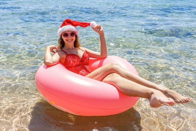 Vrouw in kerstman hoed ontspannen op opblaasbare donut in zee