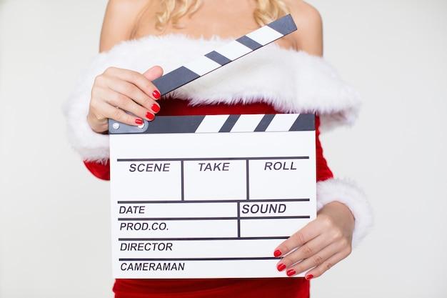 Vrouw in kerstman kostuum poseren met clapperboard