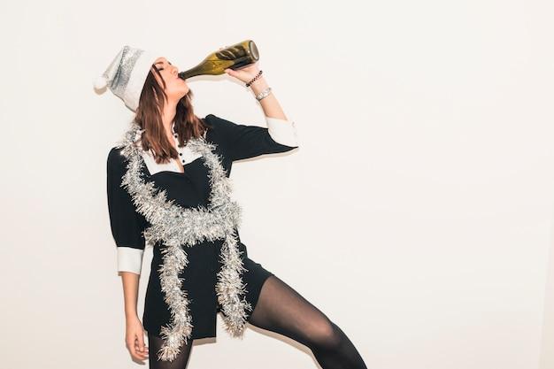 Vrouw in kerstmanhoed het drinken champagne van fles