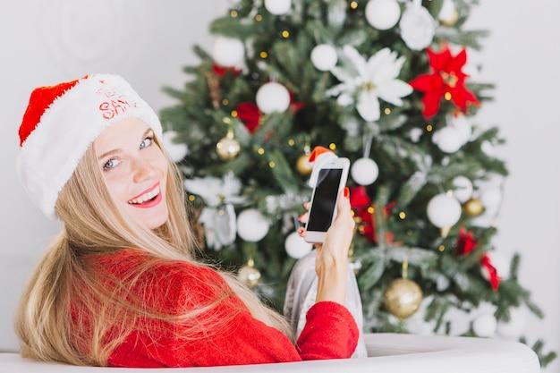 Vrouw in kerstmanhoedzitting met telefoon