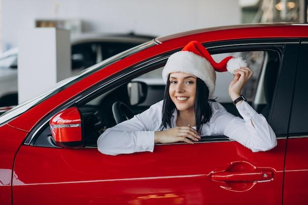 Vrouw in kerstmuts bij de rode auto in een autoshowroom