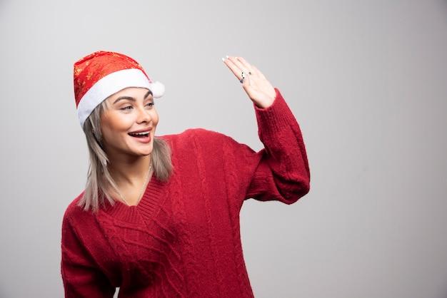 Vrouw in kerstmuts die iemand begroet op een grijze achtergrond.