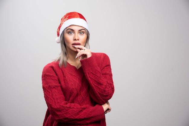 Vrouw in kerstmuts die intens op grijze achtergrond denkt.