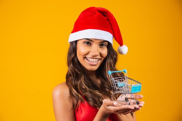 Vrouw in kerstmuts doet kerstinkopen. ze laat een minikarretje zien