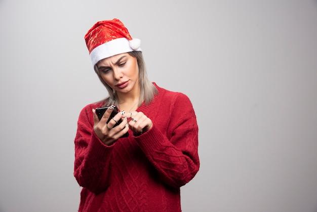 Vrouw in kerstmuts kijken naar mobiele telefoon.
