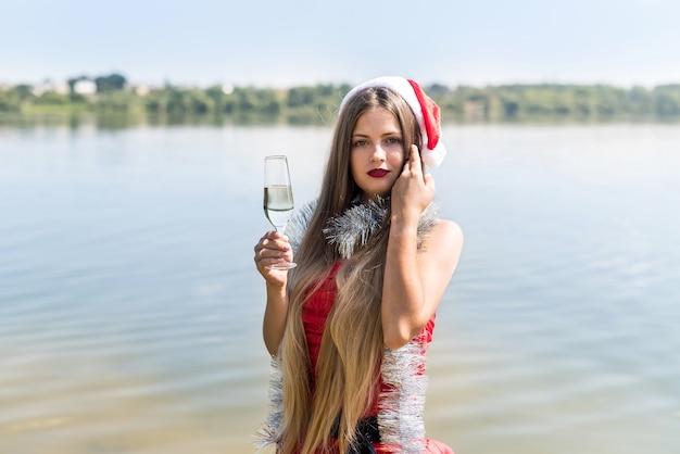 Vrouw in kerstmuts met glas champagne aan de kust