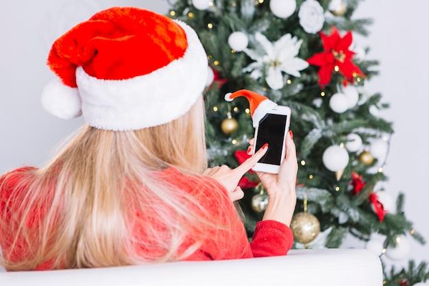 Vrouw in kerstmuts met telefoon in handen