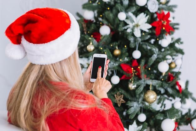 Vrouw in kerstmuts met telefoon