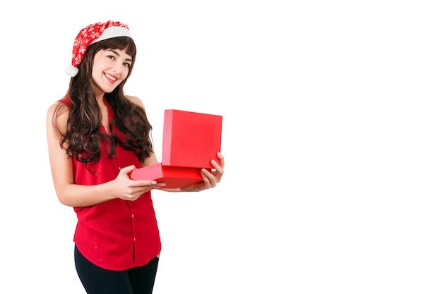 Vrouw in kerstmuts opening kerstcadeau doos