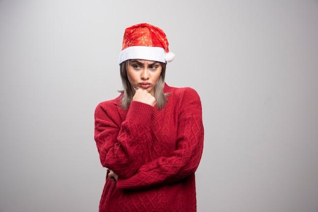 Vrouw in kerstmuts staande boos op grijze achtergrond.
