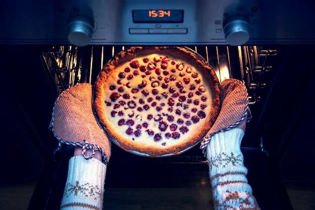 Vrouw in kersttrui haalt frambozen shortcake uit de oven.