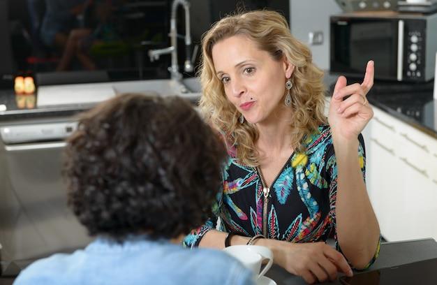 Vrouw in keuken die met vriend spreekt