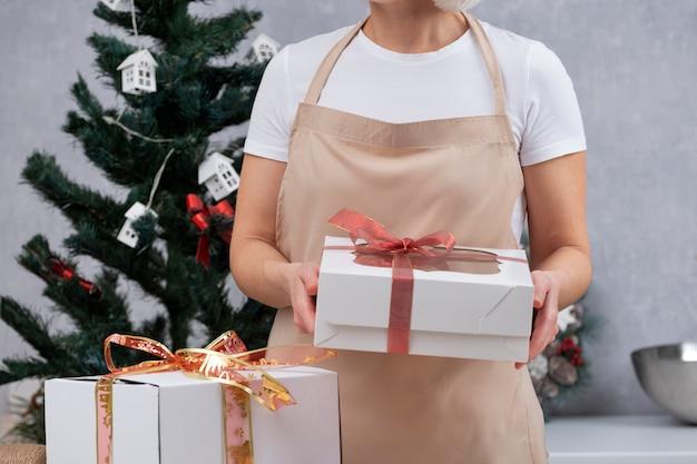 Vrouw in keuken kleed houdt geschenkdozen met kerstsnoepjes. zoete cadeaus voor het nieuwe jaar.