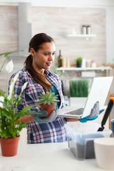 Vrouw in keuken leest over bloemen met laptop en kleine plant