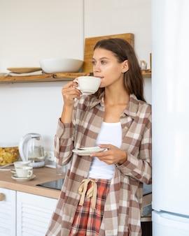 Vrouw in keuken met koffie, ochtendroutine, zelfreflectie. sociale media en digitale detox op zondag. blijf thuis en reflecteer. vrouw in pijama's die thee drinken
