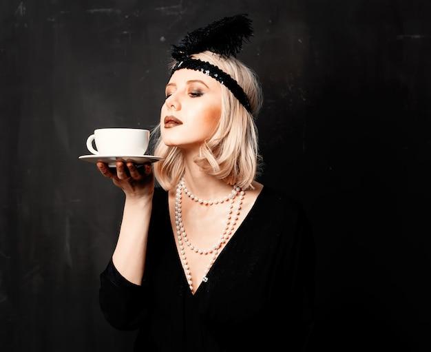 Vrouw in kleding van de jaren twintig met een kopje koffie