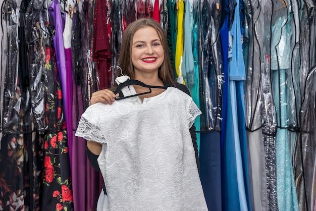 Vrouw in kledingwinkel die mooie jurk probeert