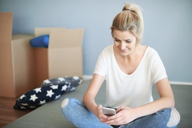 Vrouw in kleermakerszit met smartphone