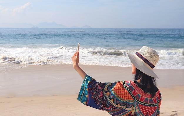 Vrouw in kleurrijke blouse nemen selfie foto's op het strand van copacabana, rio de janeiro