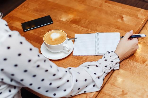 Vrouw in koffiezitting en het schrijven in notitieboekje