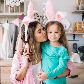 Vrouw in konijntjesoren die dochter op wang kussen