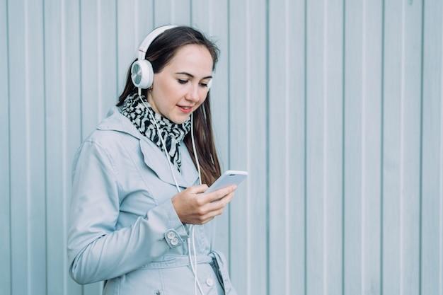 Vrouw in koptelefoon en in een grijze jas kijkt naar een smartphone