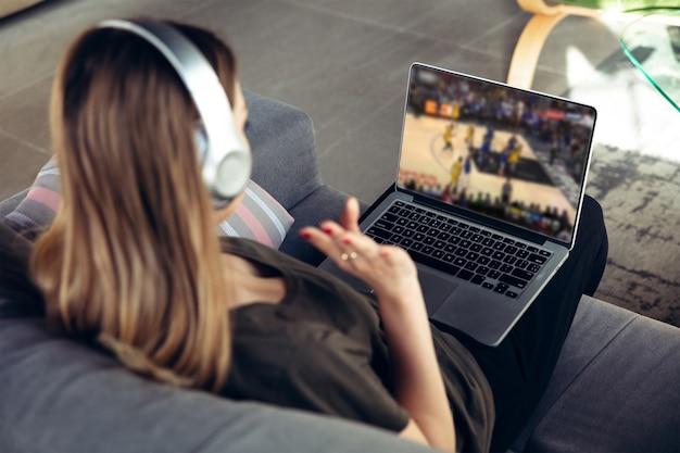 Vrouw in koptelefoon met laptop kijken naar sport, basketbal online streaming van kampioenschap. nieuwe regels tijdens de uitbraak van het coronavirus en de afsluiting van landen. concept van sport, competitie, technologieën.