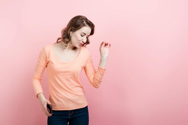 Vrouw in koptelefoon met telefoon dansen. de profielweergave.