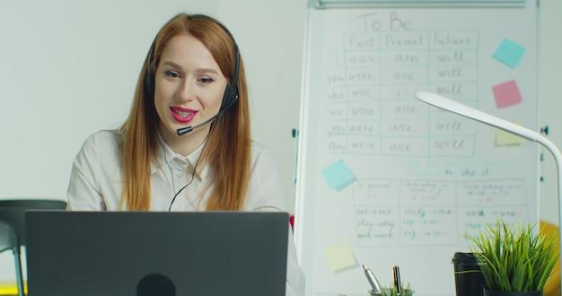 Vrouw in koptelefoon praten met studenten via videoconferentie in lege klas.