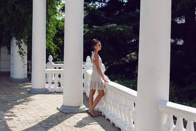 Vrouw in korte jurk en zonnebril staat in de zomer naast een hek en een witte zuil in de natuur op de krim