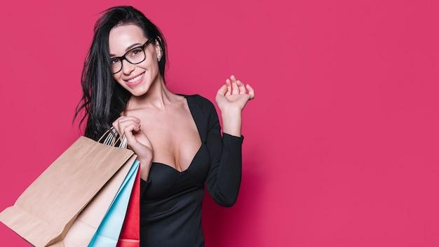 Vrouw in kostuum met papieren zakken