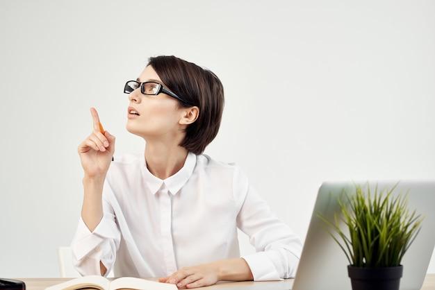 Vrouw in kostuum voor laptop documenten professionele baan geïsoleerde achtergrond